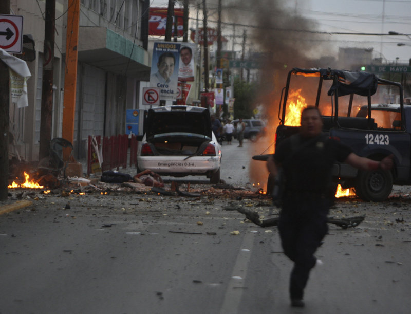 A police officer runs for cover after an attack on police patrol trucks that killed three people in the border city of Ciudad Juarez, Mexico, on Thursday. Mexican investigators ran forensic tests and determined that drug gangs used a car bomb for the first time in the attack.
