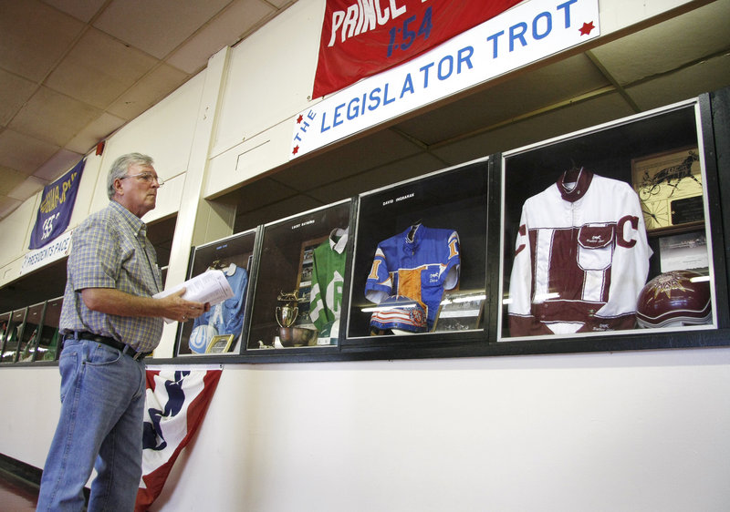 Bill Redden of Rochester, N.H., looks over the Hall of Fame silks that were on display at Scarborough Downs during its celebration.