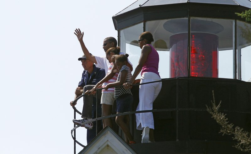 President Obama, first lady Michelle Obama, right, and daughters Malia and Sasha, center right, stand with Coast Guard Station Chief Tim Chase, left, as they visit Bass Harbor Head Lighthouse on Saturday.