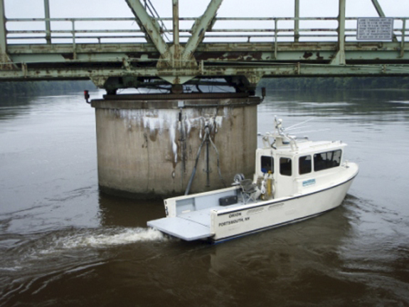 The underwater survey vessel Orion inspects one of the piers holding up the Kennebec River bridge in Richmond.