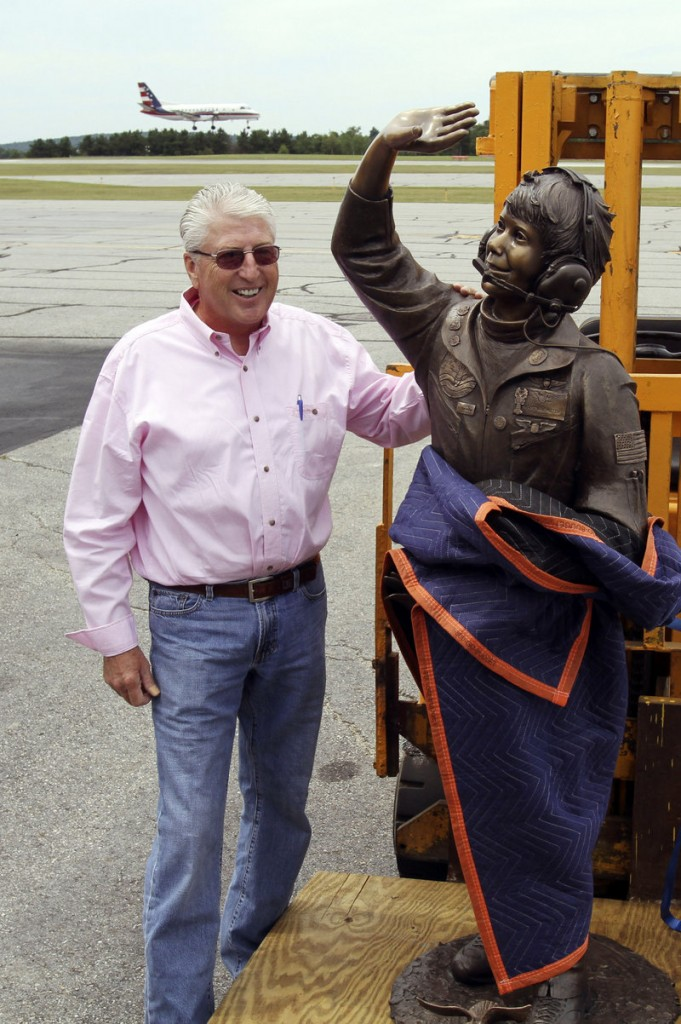 Jim Van Meter of St. George, Utah, poses Tuesday with a statue of his late daughter, Vicki, at the Augusta State Airport, where her record 1993 and 1994 flights began.
