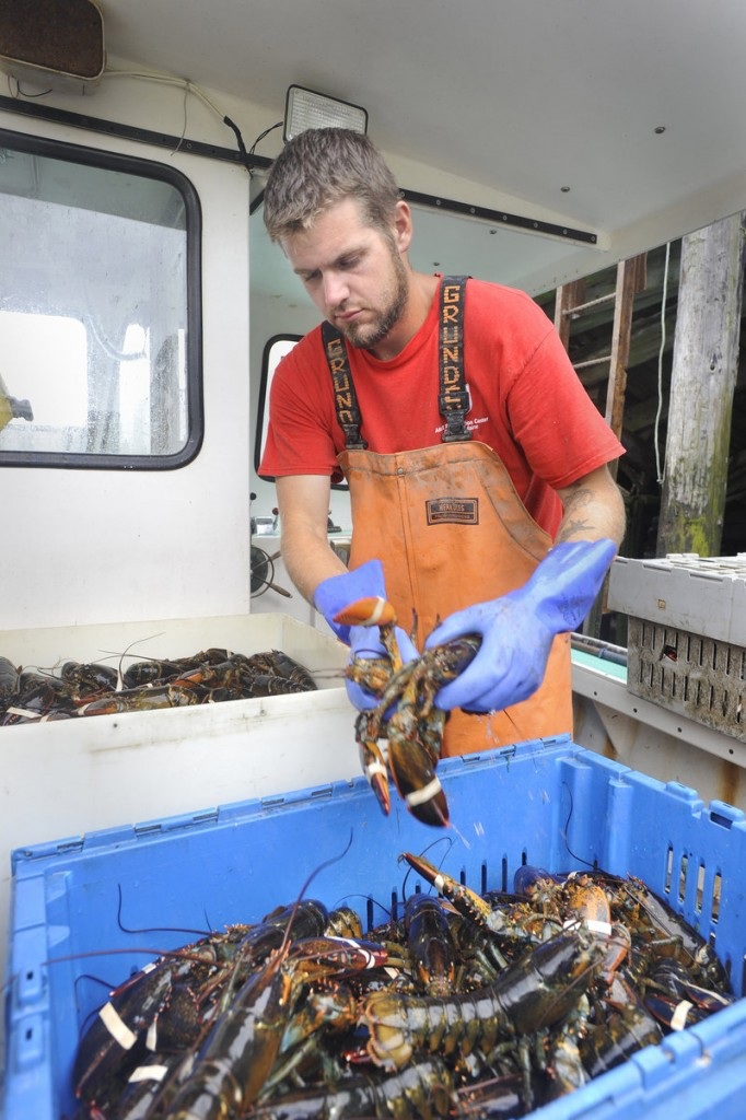 "Tom Wood, 24, serves as sternman on Yarmouth fisherman Willis Spear's lobster boat. ""Rich people just have more money and get whatever they want,"" Wood said Tuesday."
