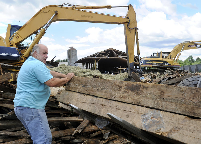 "Ed Benson salvages beams from his barn in Gorham on Thursday. The barn collapsed in a storm Wednesday night. ""It's another day on the farm,"" said Ed Benson. ""When you live on a farm, you understand these things happen."""