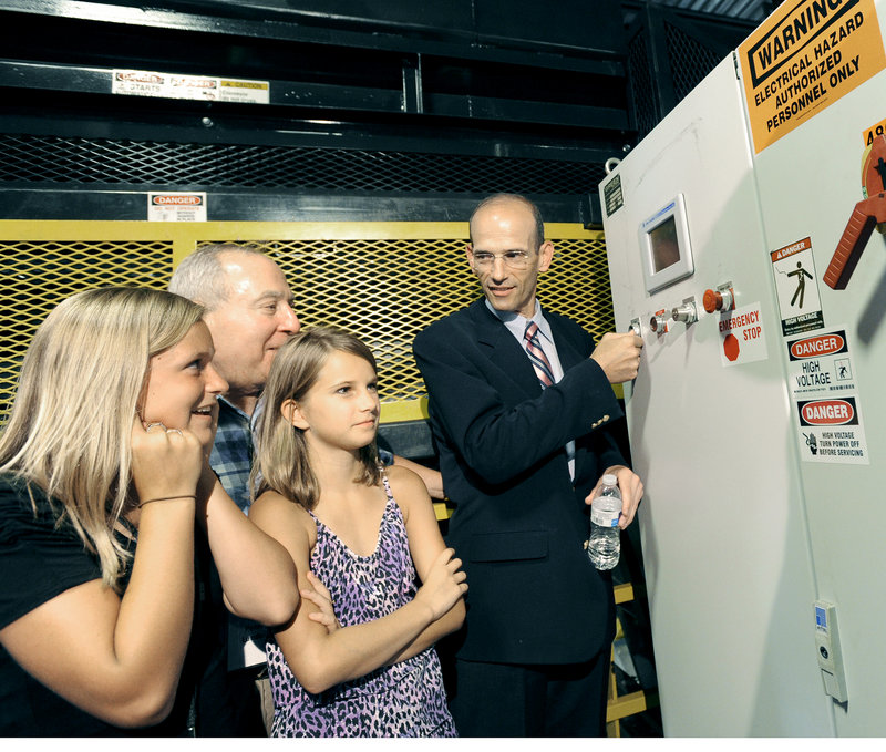 Gov. John Baldacci presses a button to start the machinery for CLYNK's new beverage container sorting system on Wednesday. From left, Emily Michaud, 12, and Peter Lunder from Scarborough, and Dana Goldy, 11, from Westboro, Mass., look on.