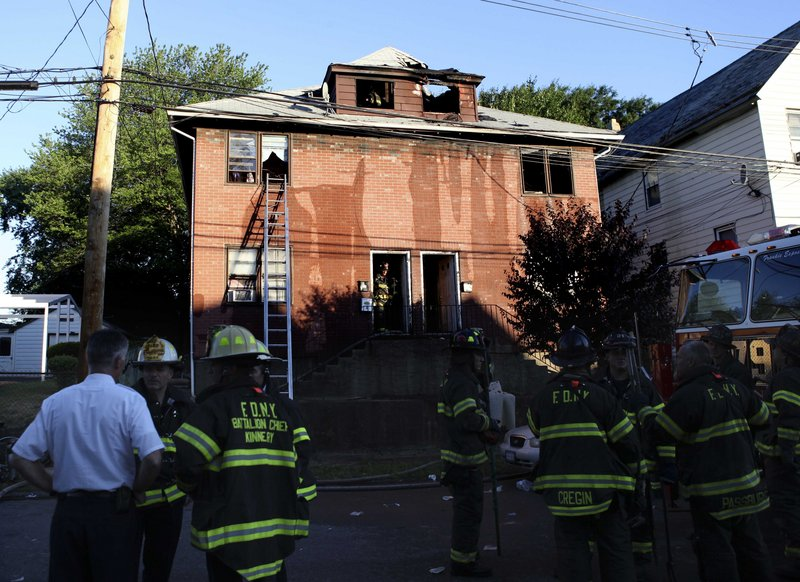 Fire officials gather after an apartment fire in Staten Island, N.Y., on Friday. Police said two children died of neck wounds and that a straight razor was found at the scene.