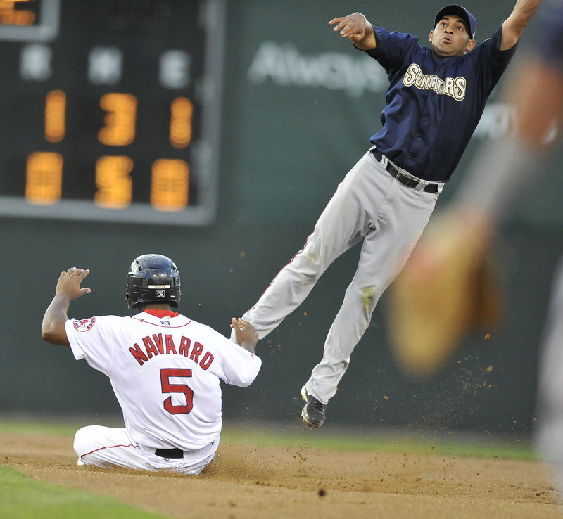Yamaico Navarro of the Portland Sea Dogs slides into second with a stolen base as Ofilio Castro of Harrisburg attempts to take down a throw that landed in center field.