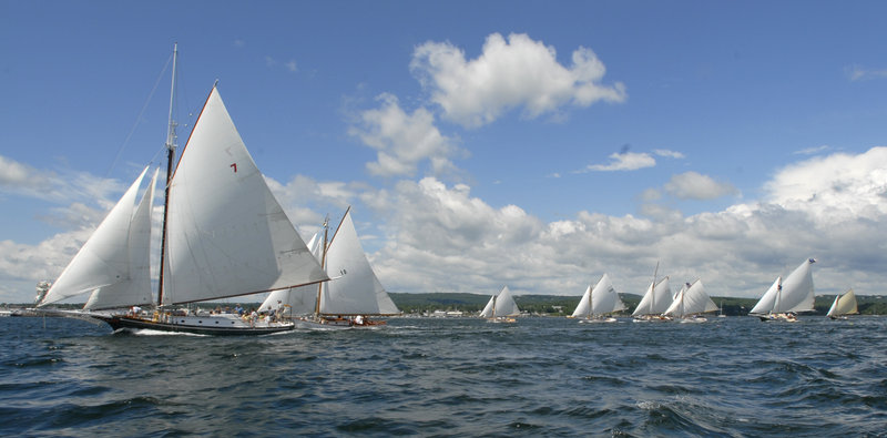 About two dozen sailboats race across the starting line during the Friendship Sloop Society's 50th annual Homecoming and Rendezvous race around Rockland Harbor on Thursday.