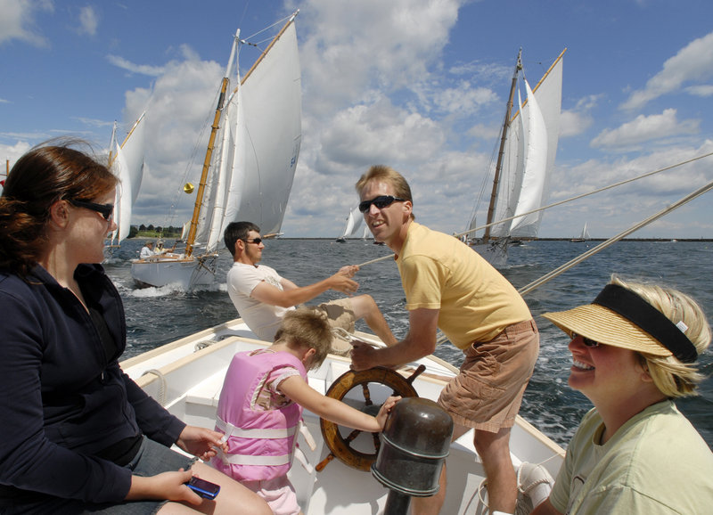 Wayne Cronin, center, steers Rights of Man, his Friendship sloop, across the starting line during a race in Rockland Harbor on Thursday. A member of the Friendship Sloop Society, Cronin is accompanied by his crew, from left to right, Kyla Prior, Ian Anderson, Ashleigh Cronin (in life jacket), and Kirsten Cronin. The Society last week was celebrating its 50th annual Homecoming and Rendezvous race.