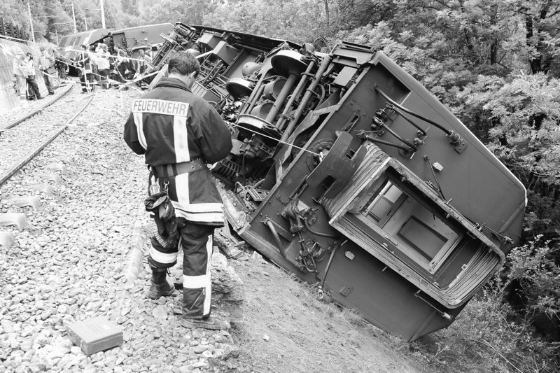 A firefighter looks at the damaged carriage of a Glacier Express passenger train at the accident site near the town of Fiesch, Switzerland, on Friday. The popular tourist train derailed in the Alps, leaving one person dead and 42 others injured.