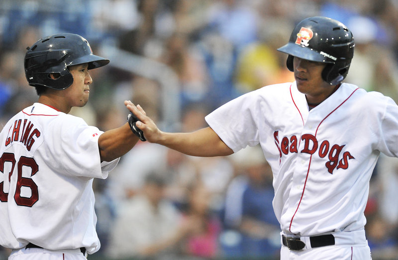 Chih-Hsien Chiang, right, of the Portland Sea Dogs is welcomed by Ray Chang after scoring in the second inning at Hadlock Field.
