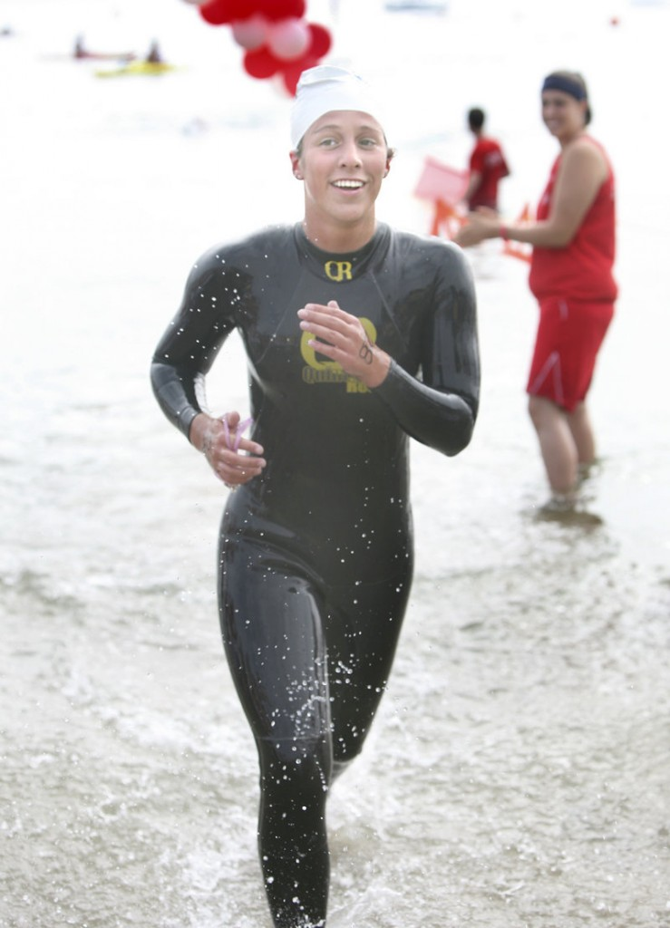 Kristen Desrosiers of Gorham is all smiles as she emerges from the water as the first female finisher in the 2.4-mile swim from Peaks Island across Casco Bay.