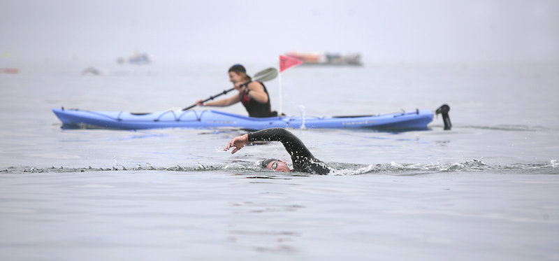 With a kayaker for company, Matthew Libby of Freeport strokes toward the finish of the Peaks to Portland open-water swim on Saturday.
