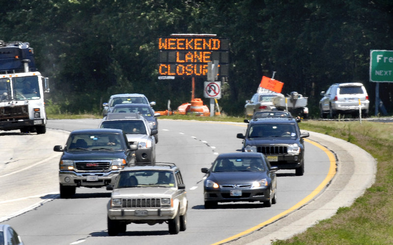 Traffic in the southbound lanes passes a sign Monday warning northbound motorists on Interstate 295 in Yarmouth about the weekend lane closing. This past weekend there were backups of up to six miles and hour-long delays.
