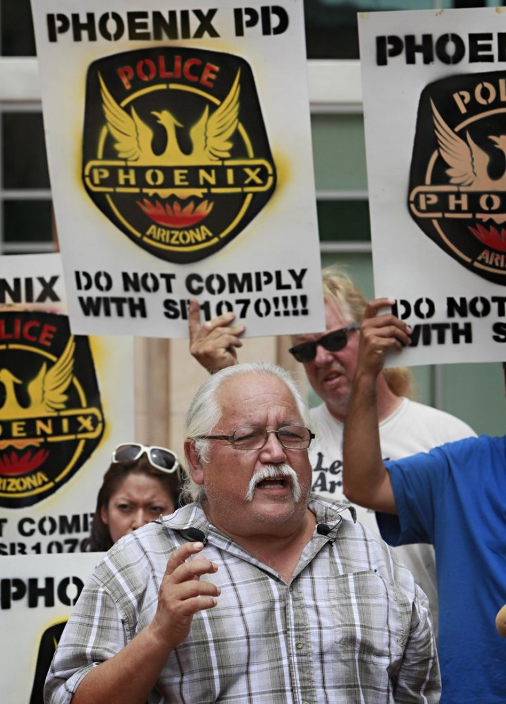 Salvador Reza petitions outside City Hall in Phoenix on Tuesday against the state's new immigration law.