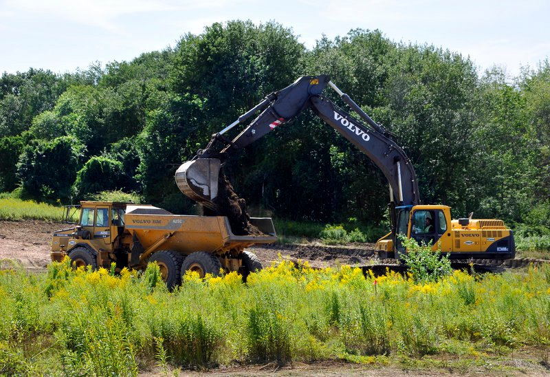 Workers create a holding pond as site preparation begins Tuesday on Eastman Meadows, a 40-acre project off Eastman Road near the Purpoodock Club in Cape Elizabeth.