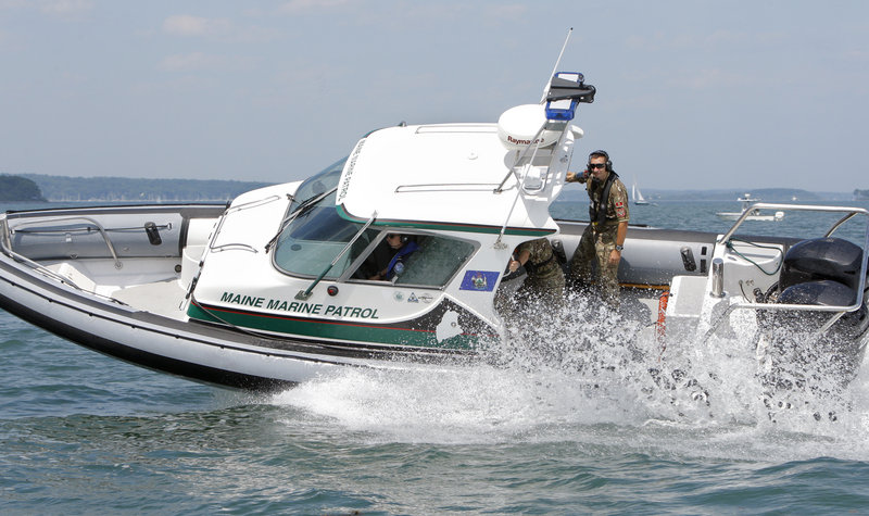 Montenegrin navy members hold on as a Maine Marine Patrol boat takes a tight turn during training on Casco Bay on Wednesday.