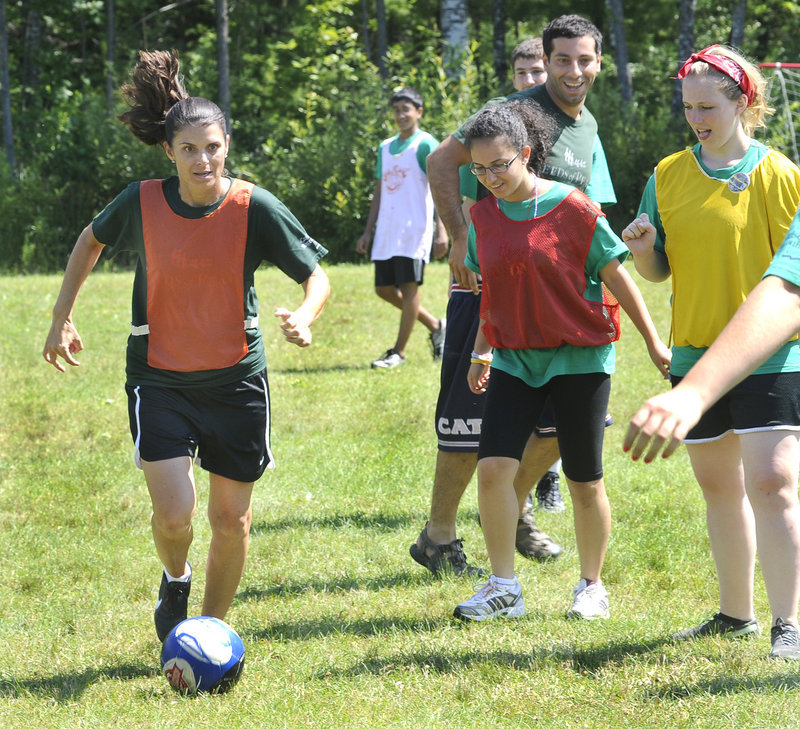 "Mia Hamm, left, gives a soccer clinic to campers Thursday during a visit to the Seeds of Peace Camp in Otisfield. ""This is ... beyond my expectations,"" she said. ""It's emotional."""