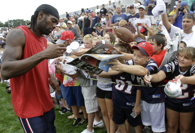 Randy Moss, signing autographs Thursday during the first day of training camp for the New England Patriots, will be one of the players needed to return the team to the top.