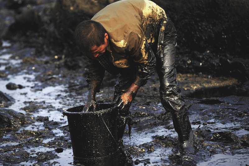 A worker cleans up oil in the Nantuo Fishing Harbor after a spill in Dalian in northeast China. The Chinese government says 461, 790 gallons have spilled, but an American oil spill expert puts the number at 18 to 27 million gallons.