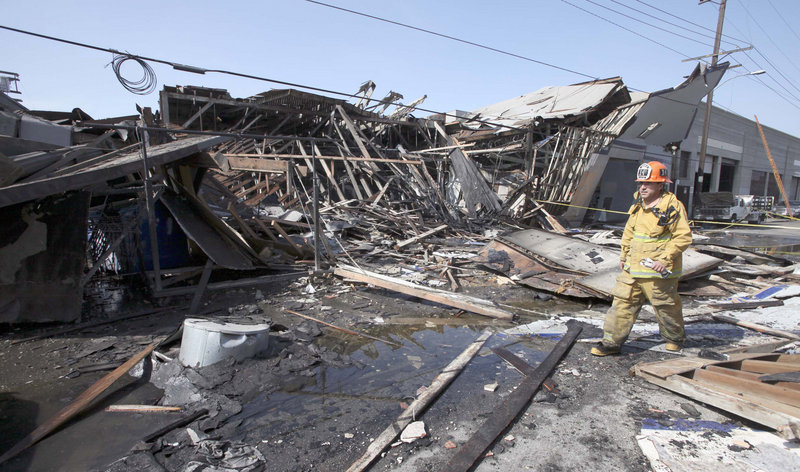 A Los Angeles firefighter walks past a partially collapsed building where an apparent natural gas explosion occurred. The explosion also hurled two workers into the street, killing one and leaving the other in critical condition, officials said.