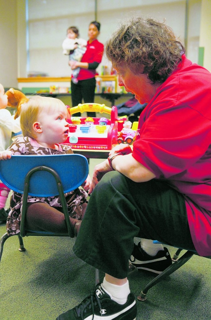 YMCA child sitter Rosalind Romero plays with Reef Hall, 16 months old, at the McBurney YMCA drop-in day care center in New York. A new study by Columbia University researchers finds that babies raised by working mothers don't necessarily suffer cognitive setbacks.