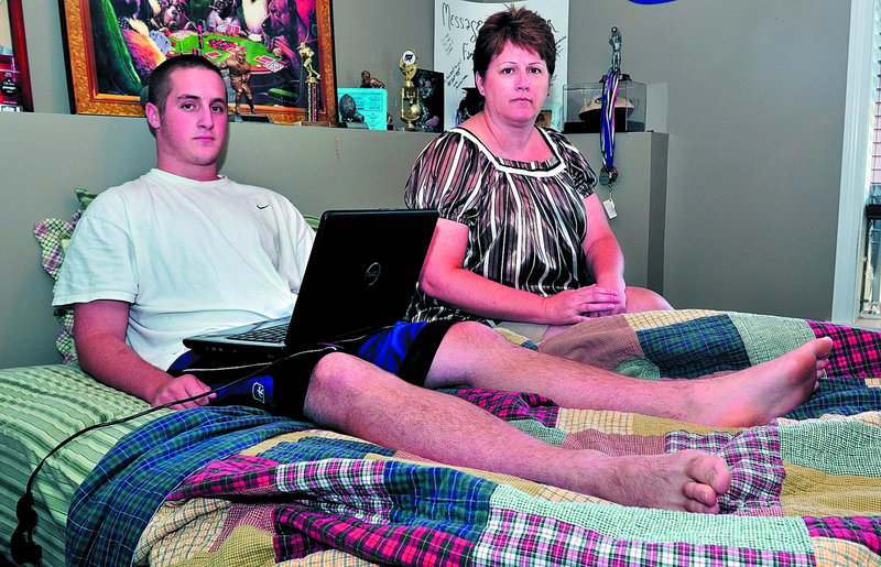 Nathan Natole, shown with his mother, Pam, uses his laptop at their home in Oakland. He was recharging the computer in his bedroom when lightning struck nearby on July 21, causing injuries to his leg and head and leading to a seizure.