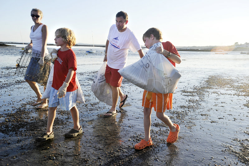 The Wood family – Seana, left, and Roger, second from right, and their sons Oliver and Aidan – participate in the Kennebunk Beach Improvement Association's annual cleanup of Kennebunk Beach on Friday evening. About 200 volunteers joined in.