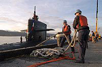 Sailors tend mooring lines as the ballistic-missile submarine USS Maine (SSBN 741) Blue crew returns from a regularly scheduled patrol Oct. 21.