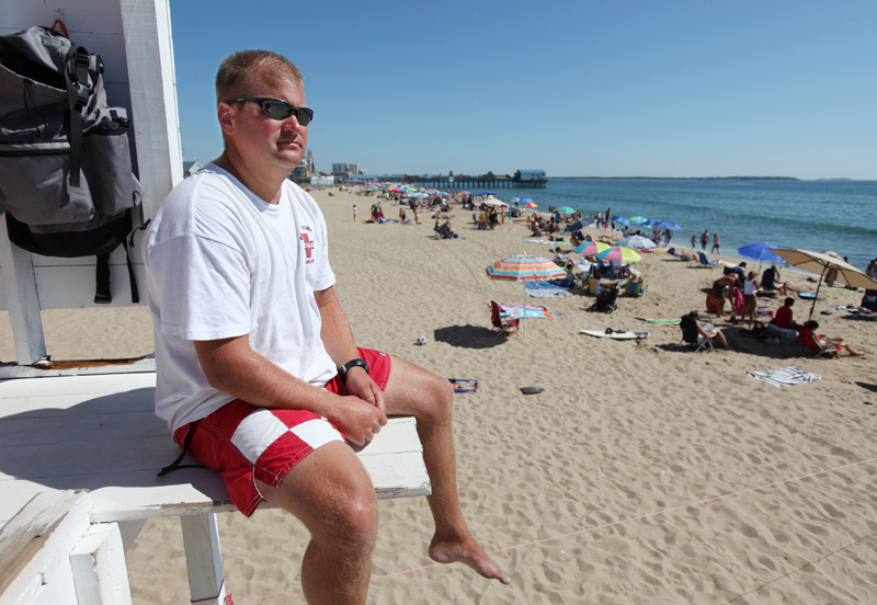 Old Orchard Beach chief lifeguard Keith Willett keeps an eye on swimmers today. Strong rip currents and crowded beaches are making it a busy summer for lifeguards in southern Maine and New Hampshire.