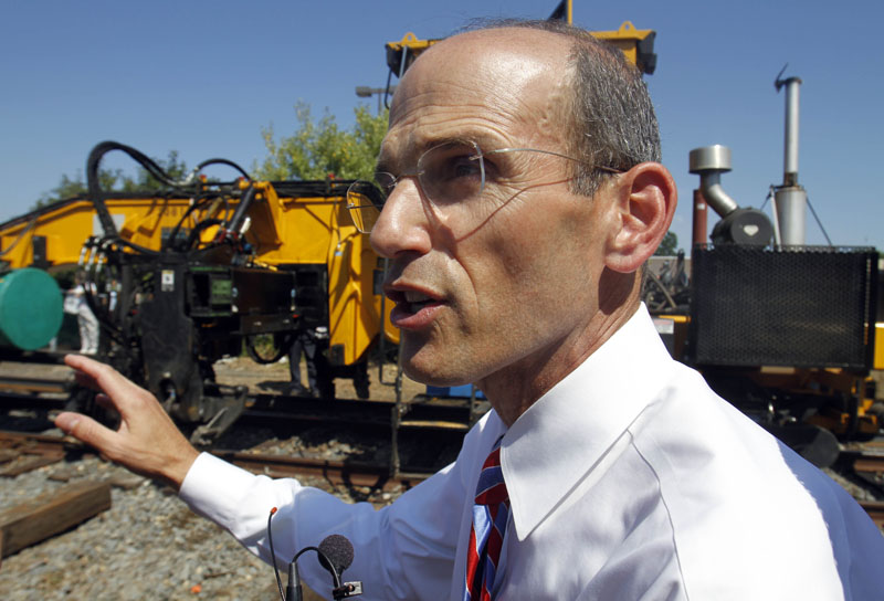 Maine Gov. John Baldacci makes comments as new rail is laid next to old tracks in Brunswick today.