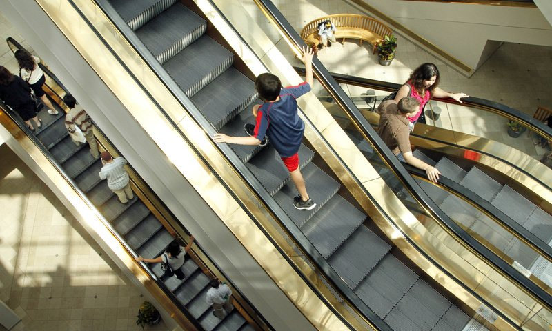 Escalator traffic is light during the lunch hour at Pioneer Square shopping center in Portland, Ore., on Tuesday. The Commerce Department today said consumer spending and income were unchanged in June, another sign of a slower economy.