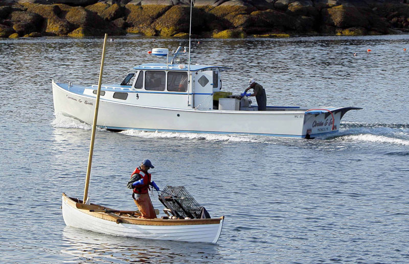 Nat Hussey hauls a trap onto his peapod by hand as a diesel-powered lobsterboat motors by off Matinicus Island.