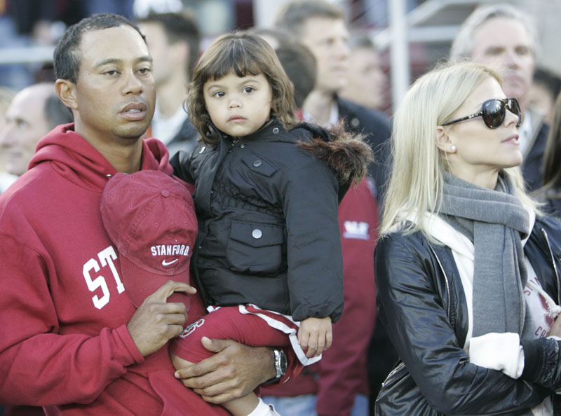In this photo taken Nov. 31, 2009, Tiger Woods, his daughter Sam and wife Elin Nordegren attend a college football game in Stanford, Calif.