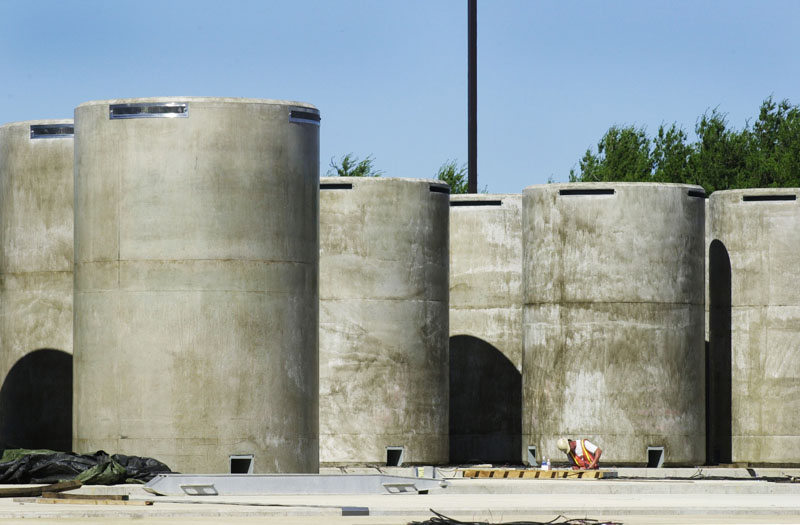These are some of the 64 steel-lined concrete containers that make up the dry cask storage facility where spent fuel assemblies are stored at Maine Yankee in Wiscasset. The assemblies are sealed in stainless steel containers inside the casks.