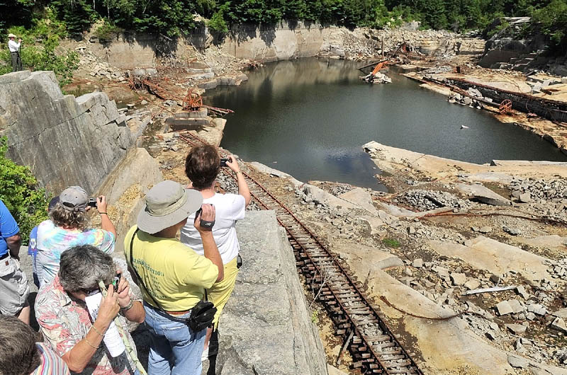 People snap pictures from the cliffs high above the Stinchfield Quarry during a tour on Sunday afternoon in Hallowell.
