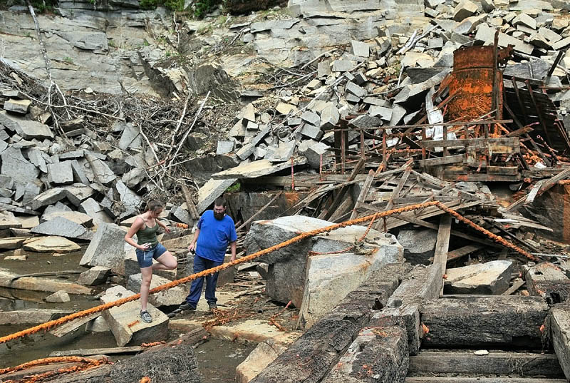 Christine Bruen, left, and Dennis Bruen climb amongst the ruins on the floor of the recently drained Stinchfield Quarry during a tour on Sunday afternoon in Hallowell.