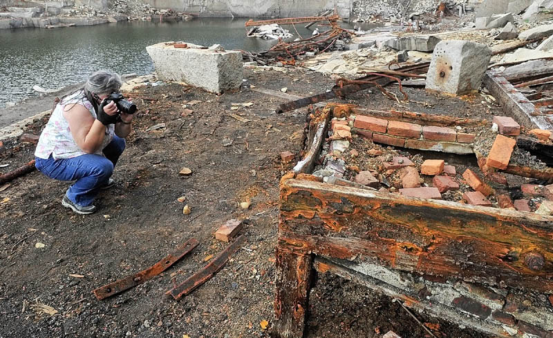 Betty Blackman, of Edgecomb, takes pictures of rusty chains amongst the ruins on the floor of Stinchfield Quarry during a tour on Sunday in Hallowell.