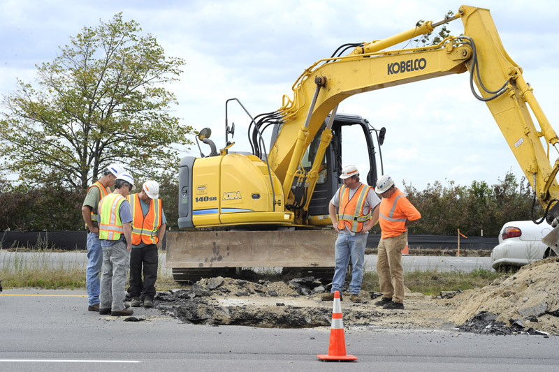 Maine Department of Transportation workers repair a sinkhole on the northbound passing lane of I-295 before Tukey's Bridge in Portland.