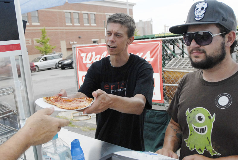 Eric Hughes serves a slice of pizza Tuesday, with his job coach, Logan Abbey, beside him. Each day they roll the food cart a quarter-mile from its storage building to the sales location.