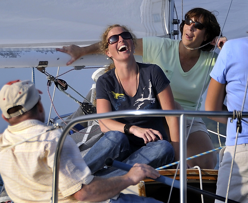 Shannon Bryan is entertained by crew member Shelly Paules, who jokingly demonstrates one of the dangers of sailing.