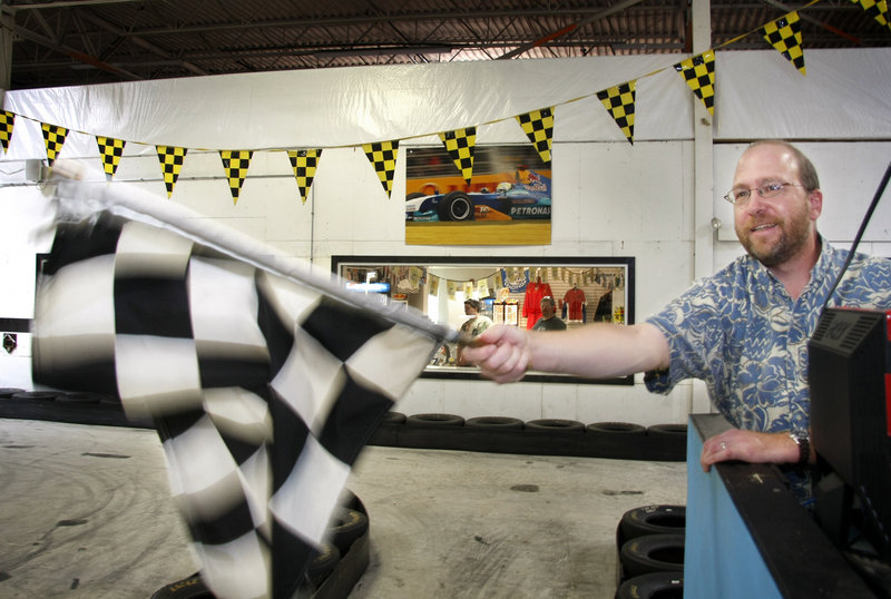 Reporter Ray Routhier waves the checkered flag to signal the end of a race at Maine Indoor Karting in Scarborough.