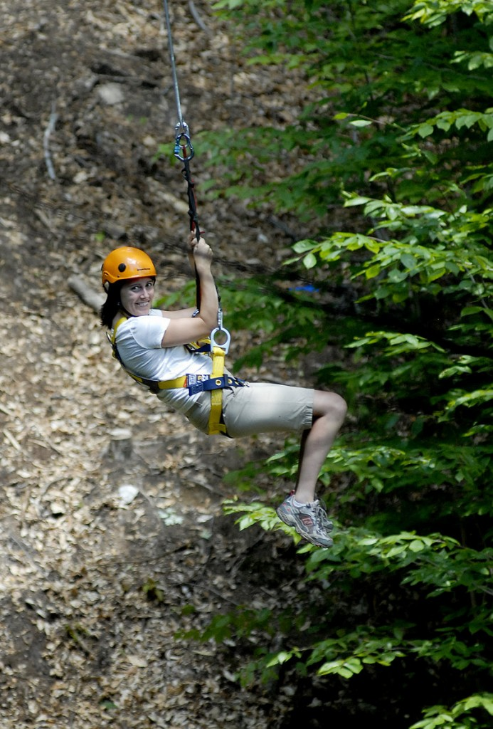 Darcy Liberty, director of communications at Sunday River, zips through an opening in the forest canopy in Newry.