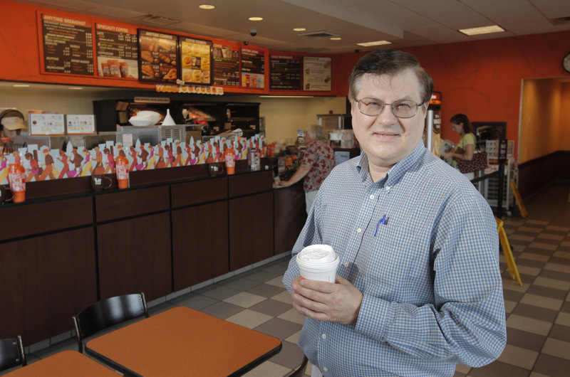 Ed Wolak, who owns 70 Dunkin' Donuts franchises in New England and New York, as well as a donut factory, stands at the shop on Gray Road in Falmouth.