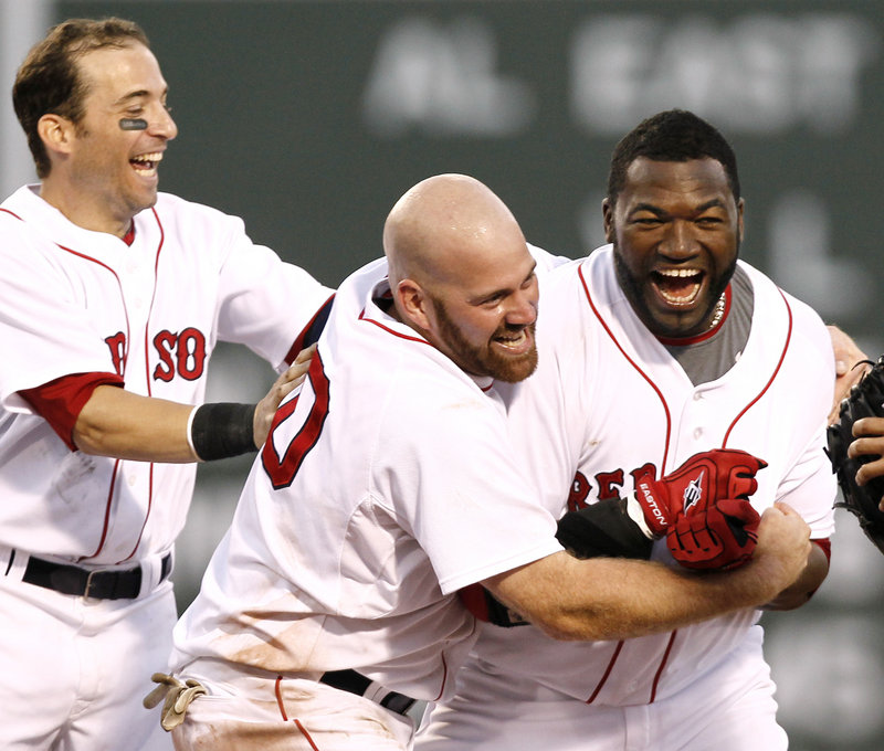 David Ortiz is mobbed by Marco Scutaro, left, and Kevin Youkilis after clearing the bases with a double in the ninth inning Saturday, giving the Red Sox a 5-4 win over Detroit on May 13, 2014.