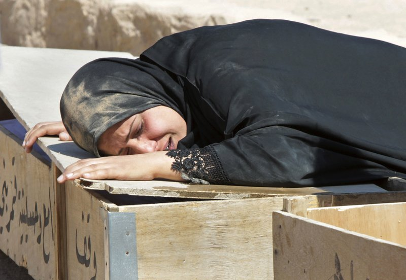 Umm Haider weeps over the coffin of her son, Ameer Hussein, 9, during his funeral July 22 in Najaf, Iraq. The family said he was killed in a bomb attack the day before. July was Iraq's deadliest month since May 2008, according to new figures.