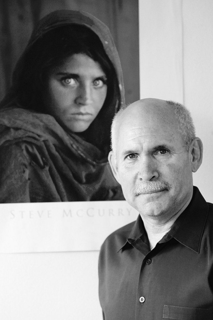 Steve McCurry poses for a portrait in New York with a poster of his iconic photograph of an Afghan refugee girl. McCurry used the last roll of Kodachrome produced to photograph the Brooklyn Bridge, Grand Central Terminal and human icons including Robert De Niro. Kodak discontinued the film last August.