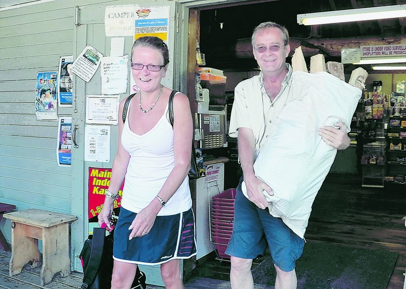 Linda Cteyr and Roch Tessier of East Angus, Quebec, head out of the Bayley's Camping Resort store Monday with enough firewood for their stay at the Pine Point campground in Scarborough. Bringing in firewood from out of state is now illegal, to deter bringing in unwanted pests in the wood. The bag of hardwood firewood costs only $10 and is cut, seasoned and sold by Tom Bayley.