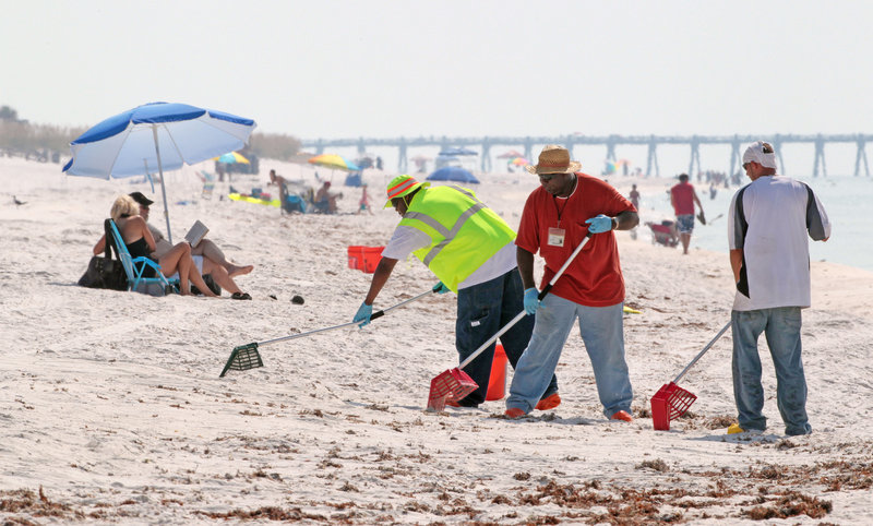 Oil cleanup workers rake for tar balls on Pensacola Beach, Fla., Sunday. Tourism is starting to pick up along the Gulf Coast with the capping of the Deepwater Horizon wellhead.