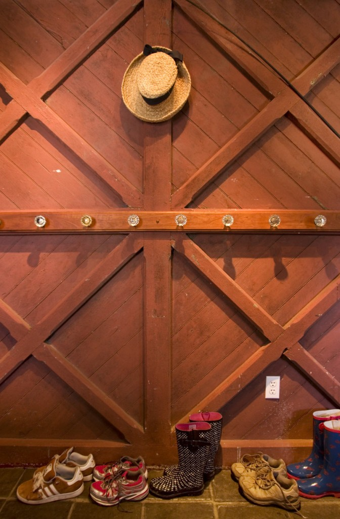 The wall of the mudroom is actually an old barn door. Coats and hats hang from antique doorknobs.