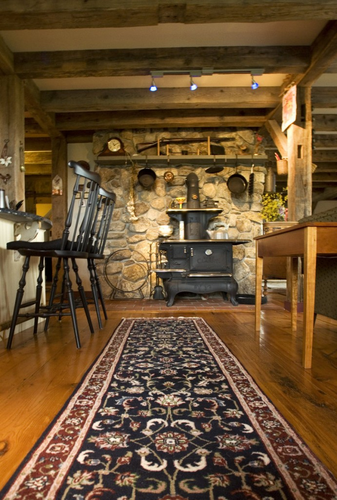 An old stove that has been refurbished sits against an interior stone wall between the kitchen and the living room.
